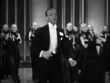 Fred Astaire dances with girls in Ginger Rogers masks.